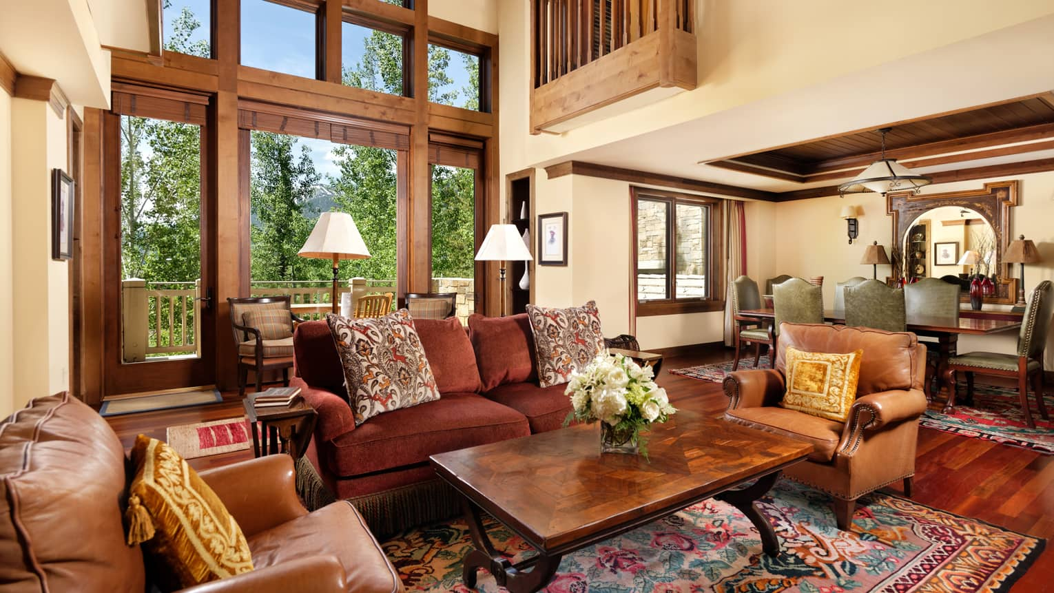 Plush sofa, brown leather armchairs under tall loft-like ceiling, windows