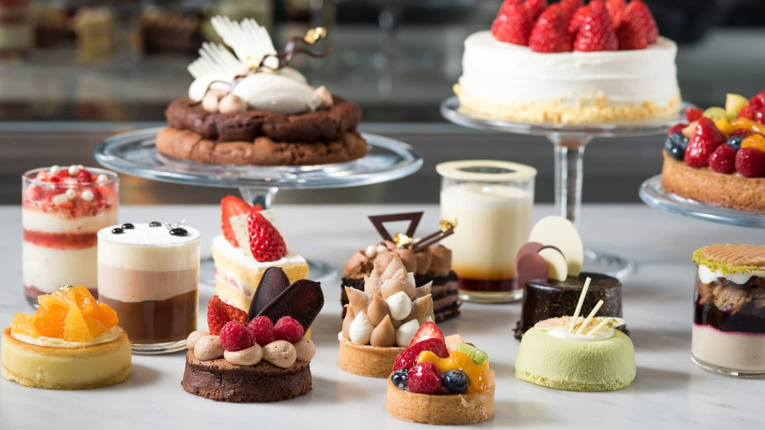 Small handmade pastries, cakes and desserts on white counter
