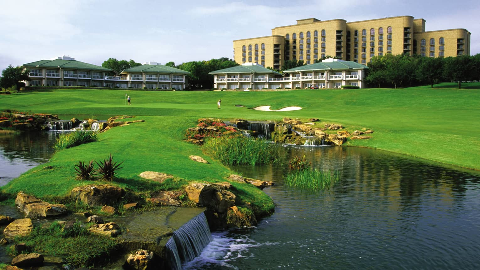 Small waterfalls, rocks, pond by golfers on green in front of TPC Four Seasons Las Colinas golf course