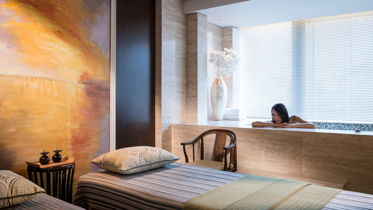 Woman rests head, arms on Spa tub beside massage table