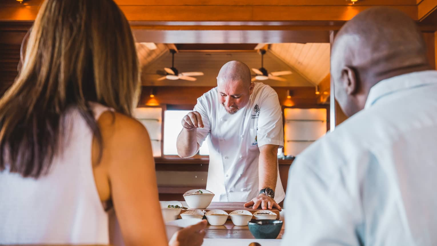 Guests watch as a chef sprinkles spices onto a special dish