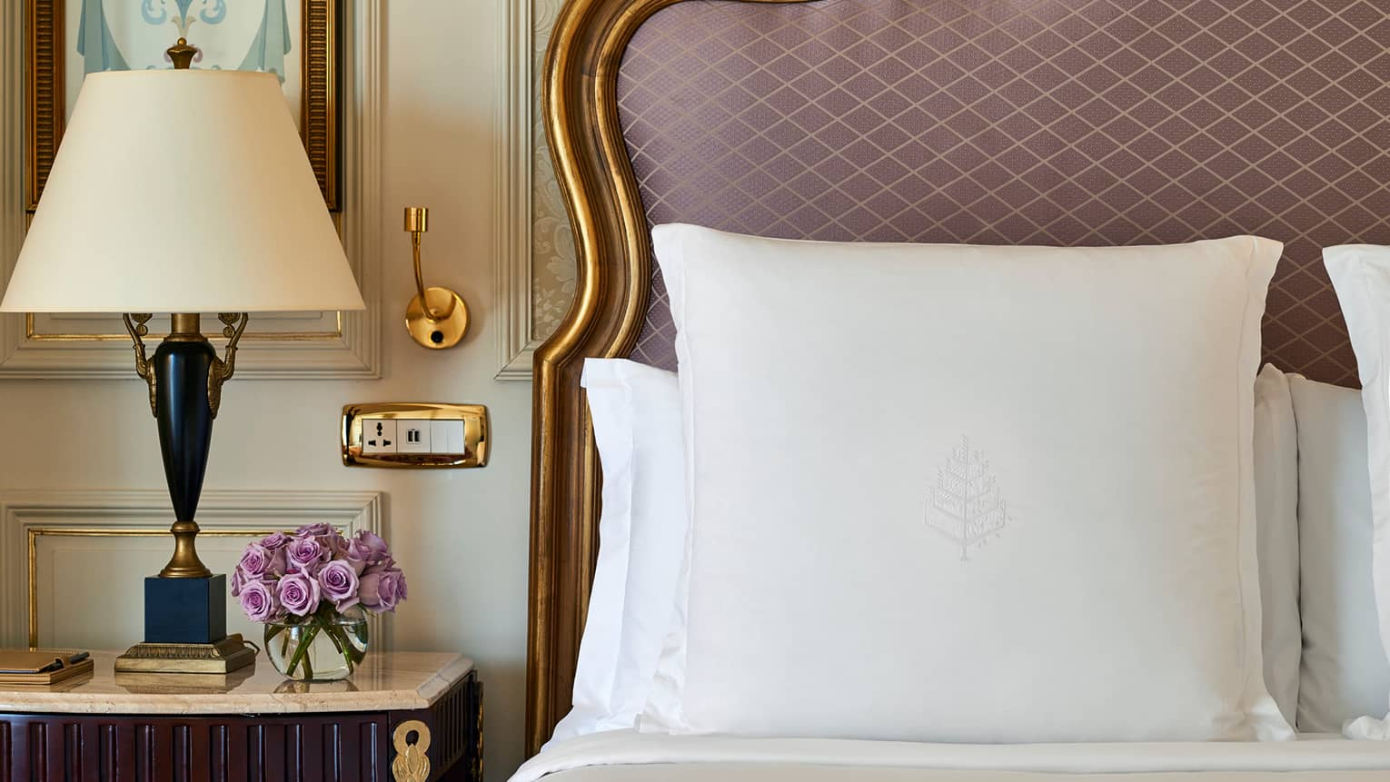 Close-up of white pillows against upholstered pink headboard with gold wood trim