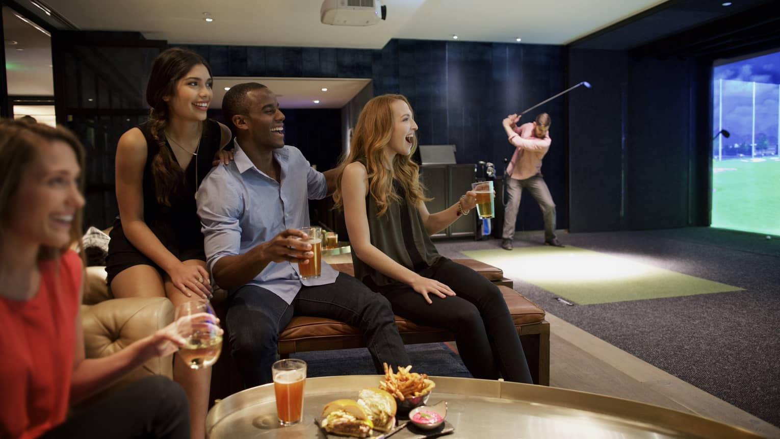 A man and three woman sip beer and cheer on a sports team in the foreground, while another man golfs in the background of a function room at four seasons hotel houston