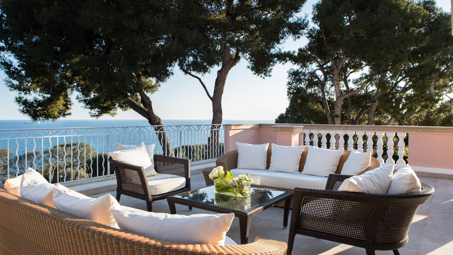 Plush patio sofas, chairs on veranda by trees, Mediterranean Sea views