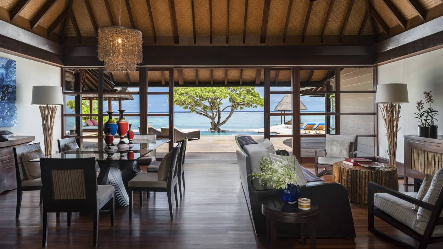 Wood-floored living room, opening up to the beach, of a Two-Bedroom Royal Beach Villa