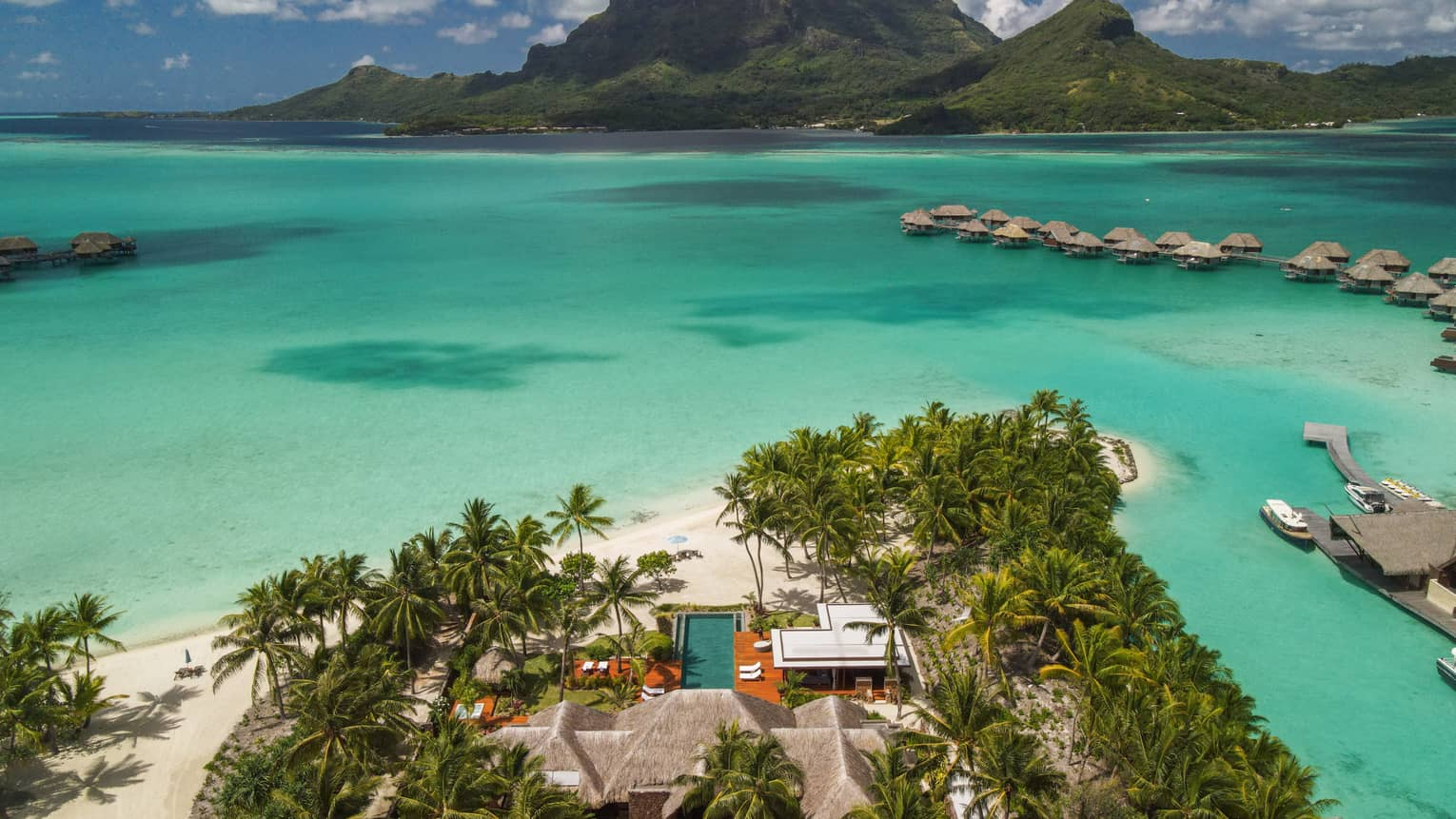 Aerial view of Bora Bora villa on edge of turquoise lagoon, looking out to overwater bungalows and mountains