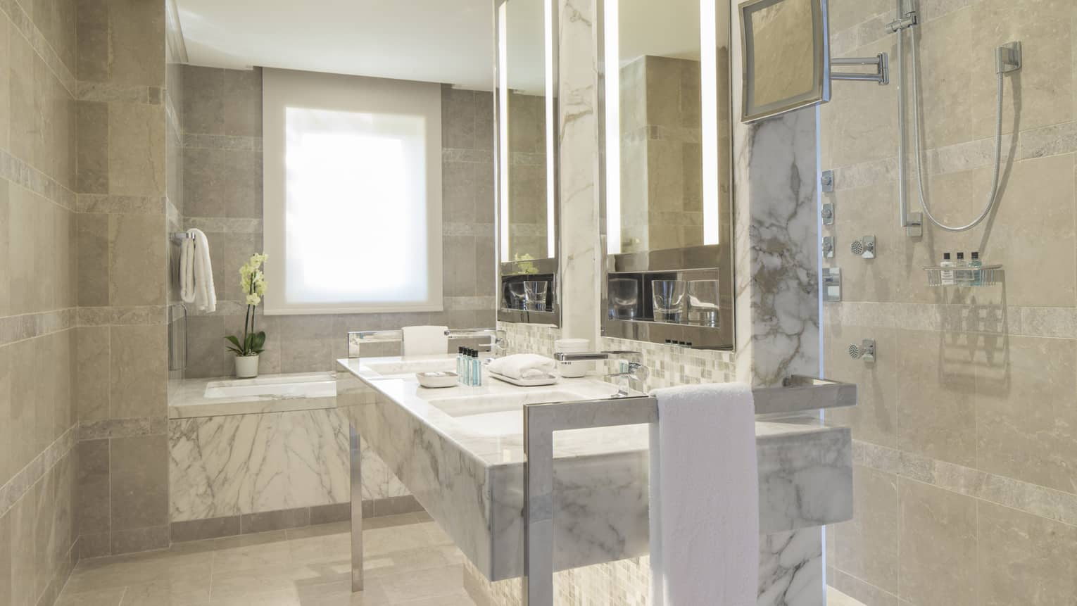 Executive Suite full white and grey marble bathroom, vanity with double sink, tub