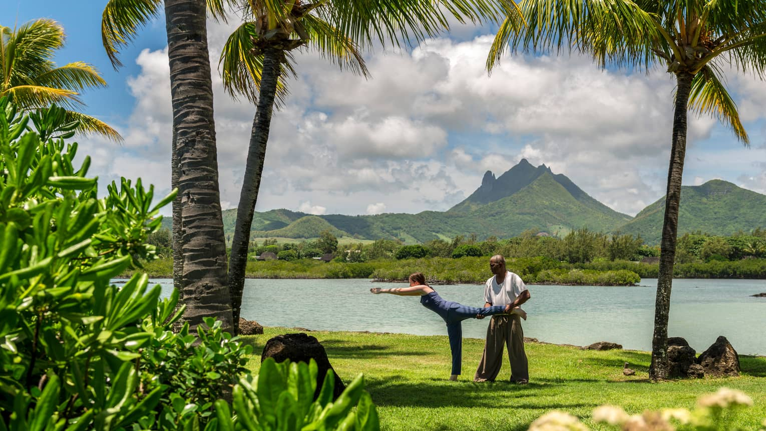 Man helps woman stretch in yoga pose on green lawn by ocean