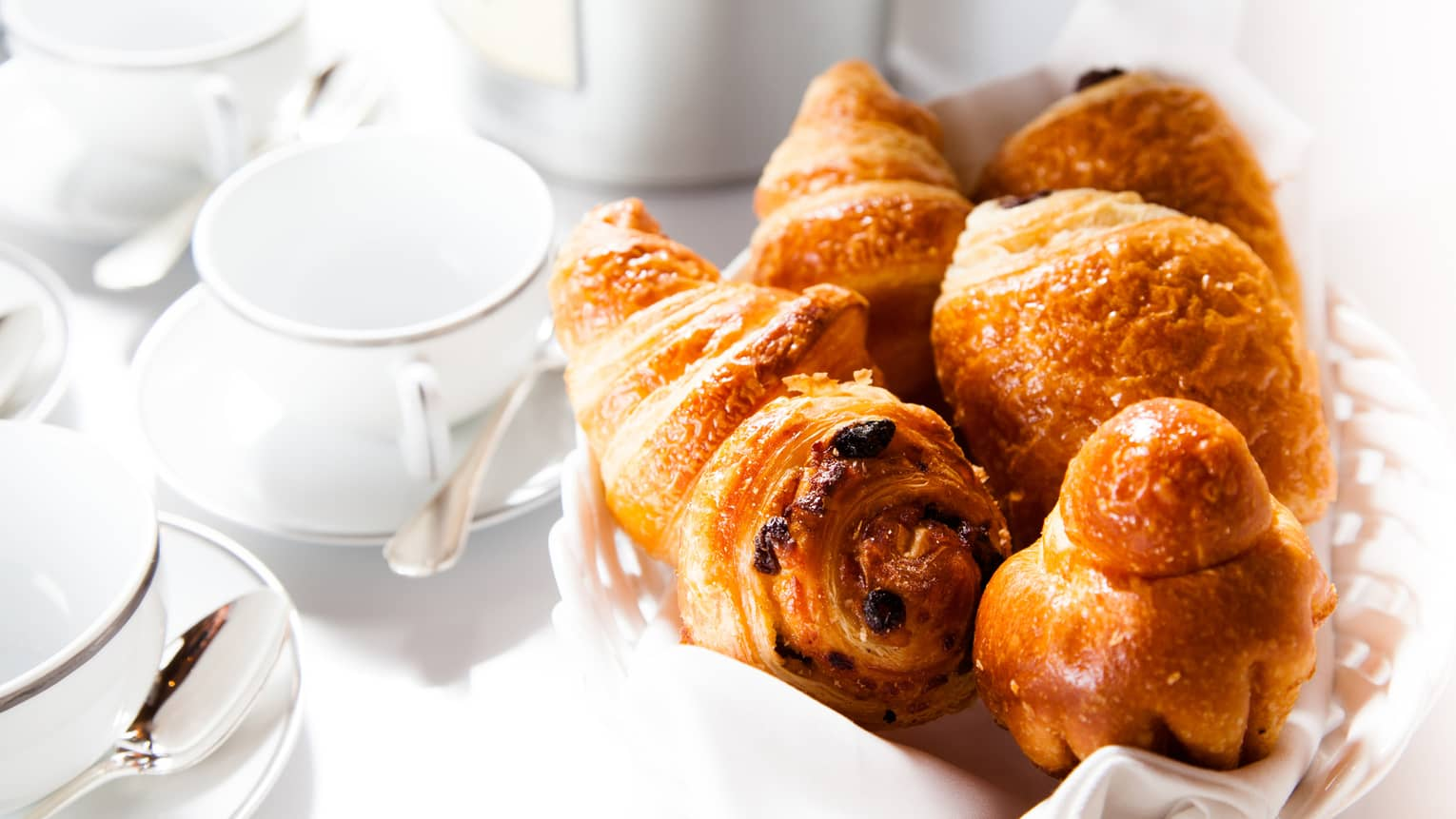 Fresh pastries, croissants in basket by white tea cups