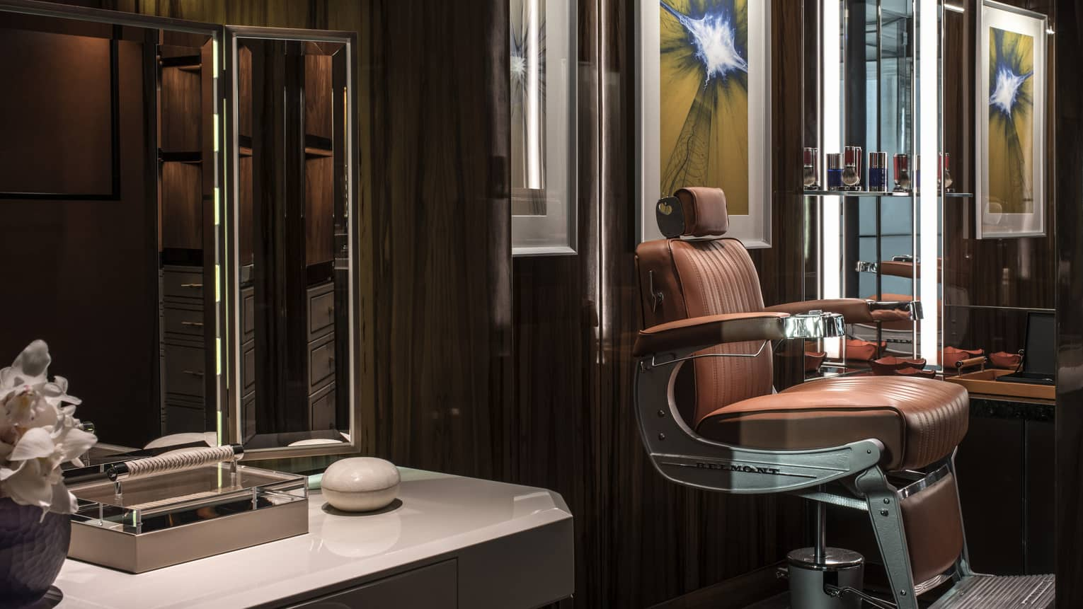 Brown leather barber chair, white counter with mirror in dimly-lit salon with dark walls