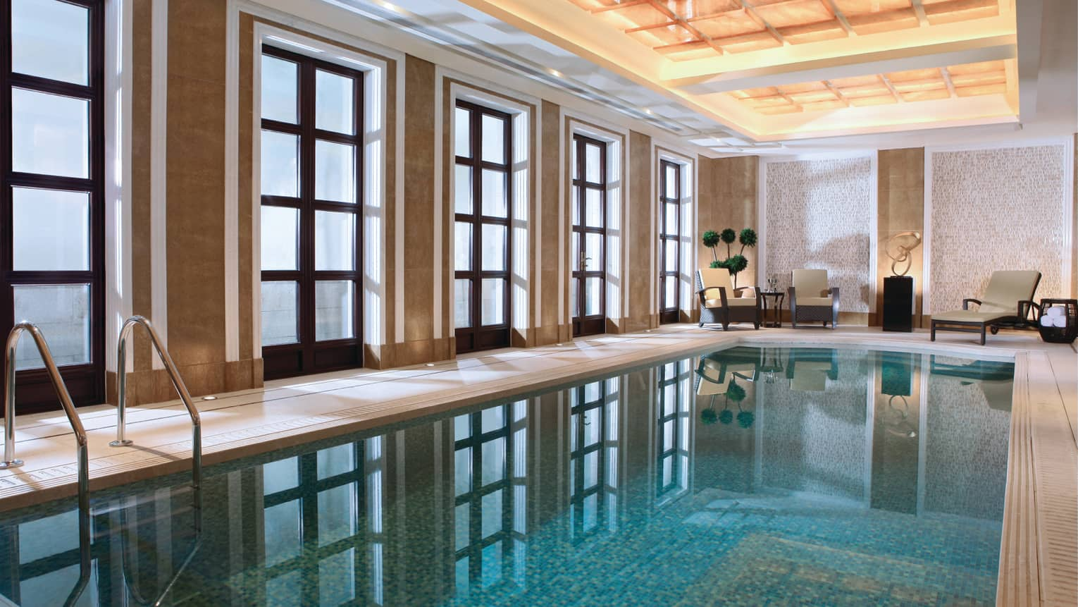 Floor-to-ceiling windows reflecting on long indoor swimming pool