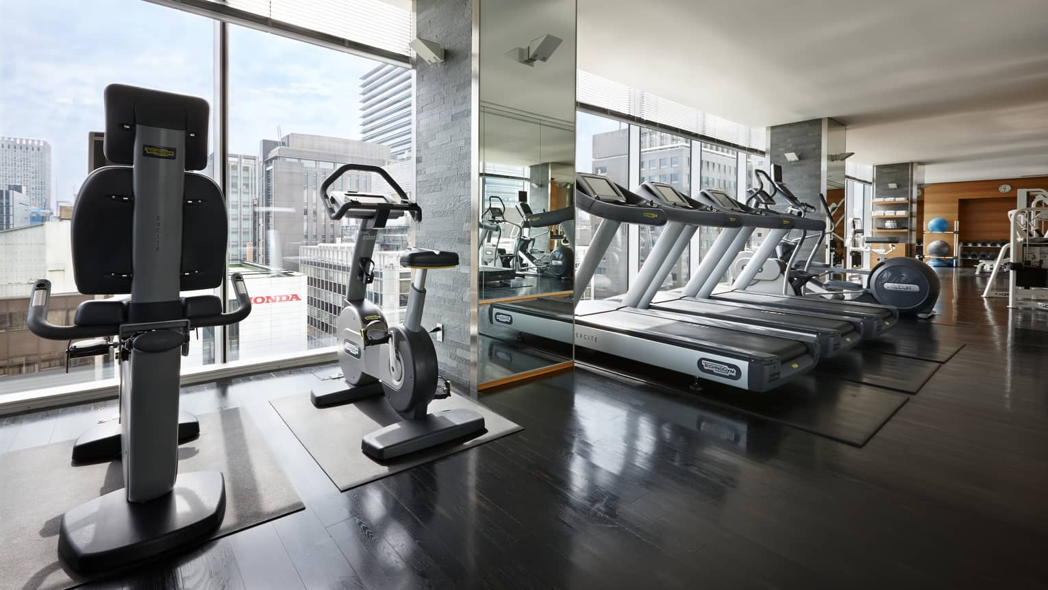 Elliptical machines, treadmills, cardio equipment by sunny window in Fitness Centre