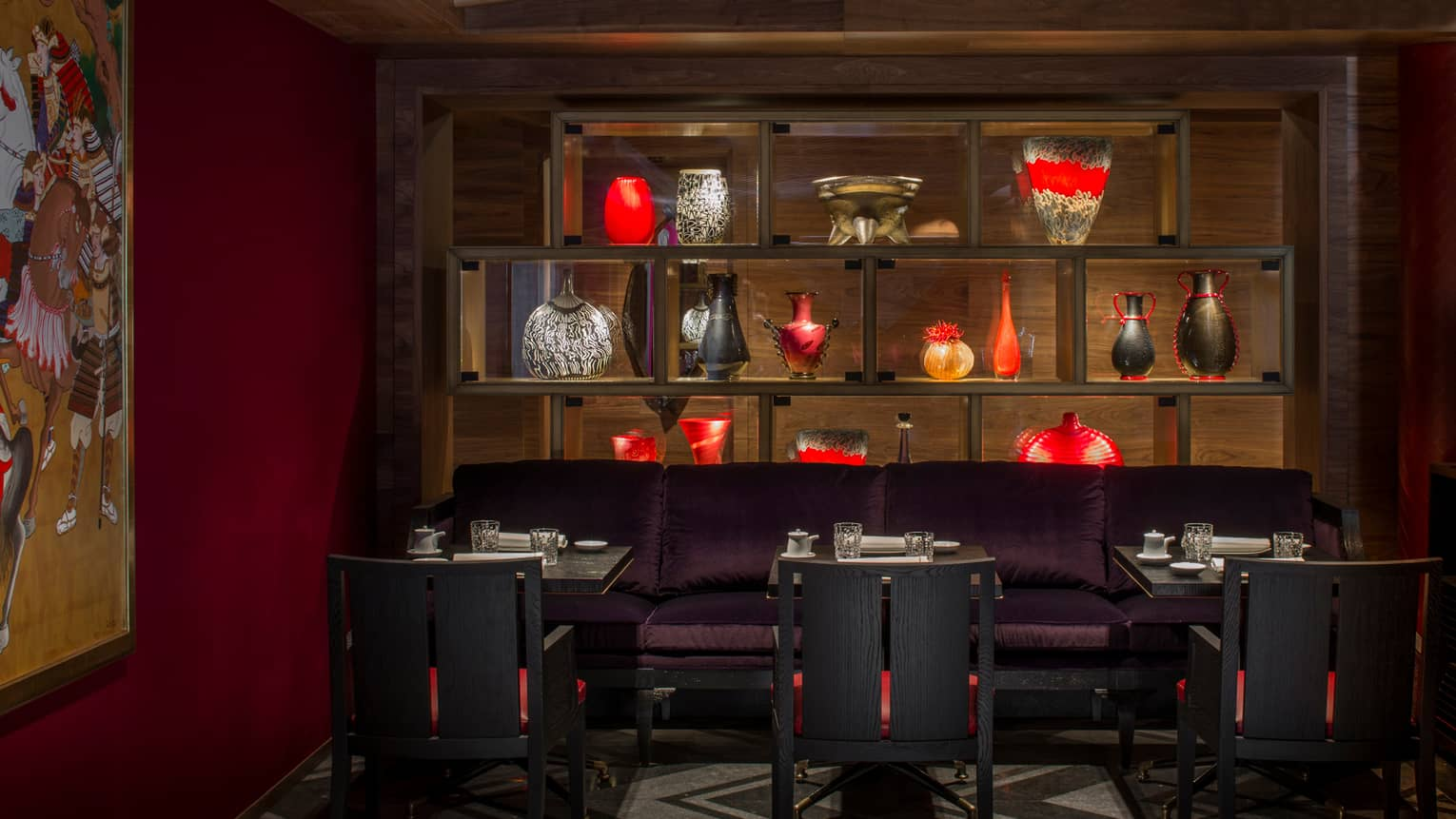 Kaito restaurant, black, red vases on shelf with lights over purple banquette, tables, colourful wall textile
