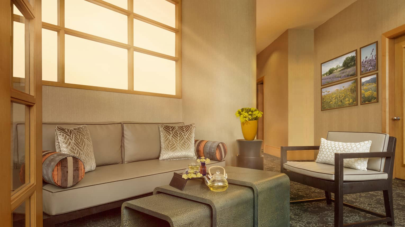 Spa seating area with couches, art on the wall, and windows letting in warm sunlight