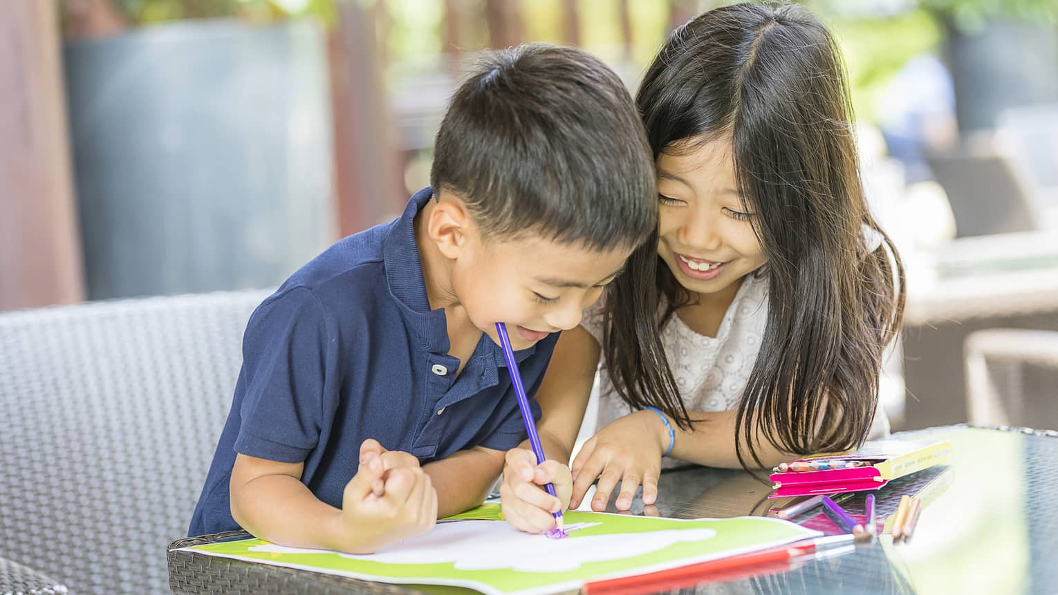 Smiling young boy and girl colouring in book with crayon