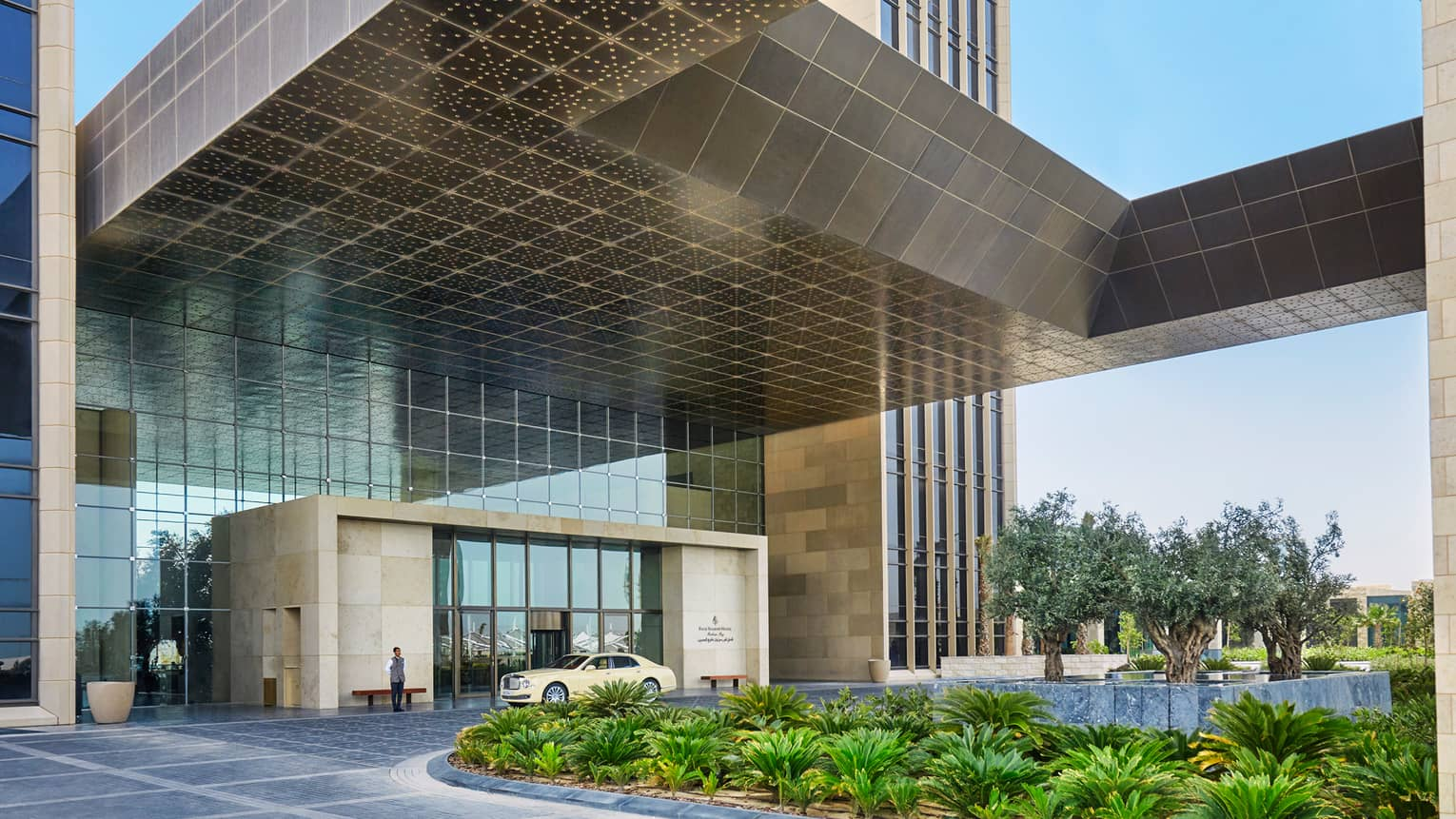 Four Seasons Hotel Bahrain Bay front entrance, car in front of door, door person, tropic garden