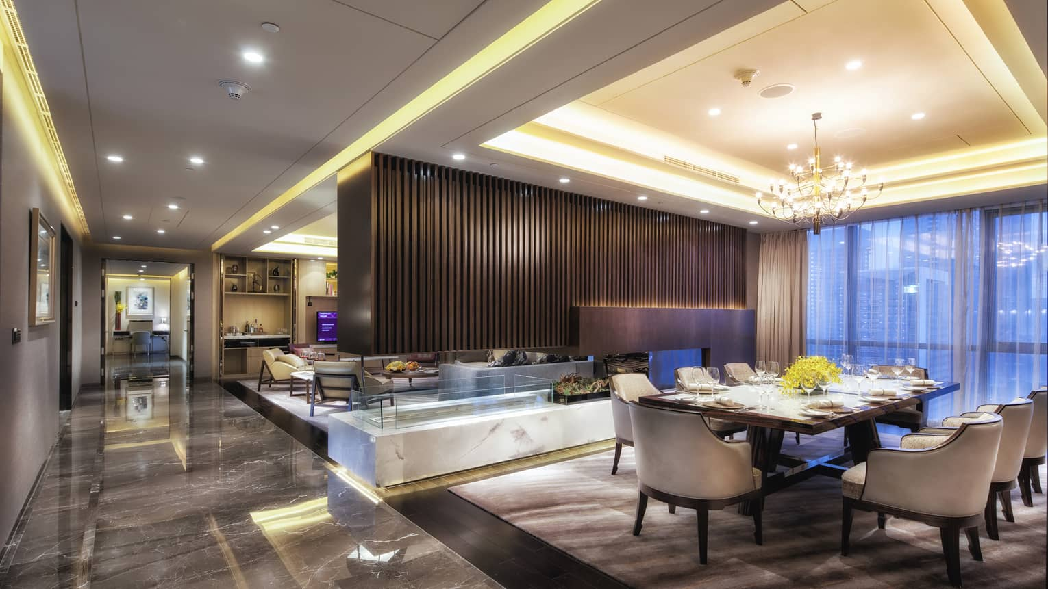 Presidential Suite large dining room, modern wood fireplace separating living room, marble floors