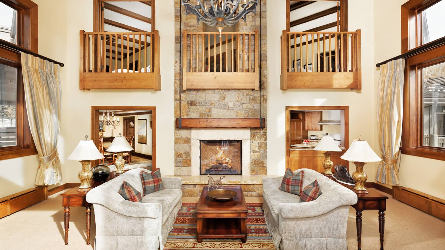 Two white sofas by tall stone fireplace with second-floor lookout, wood railings