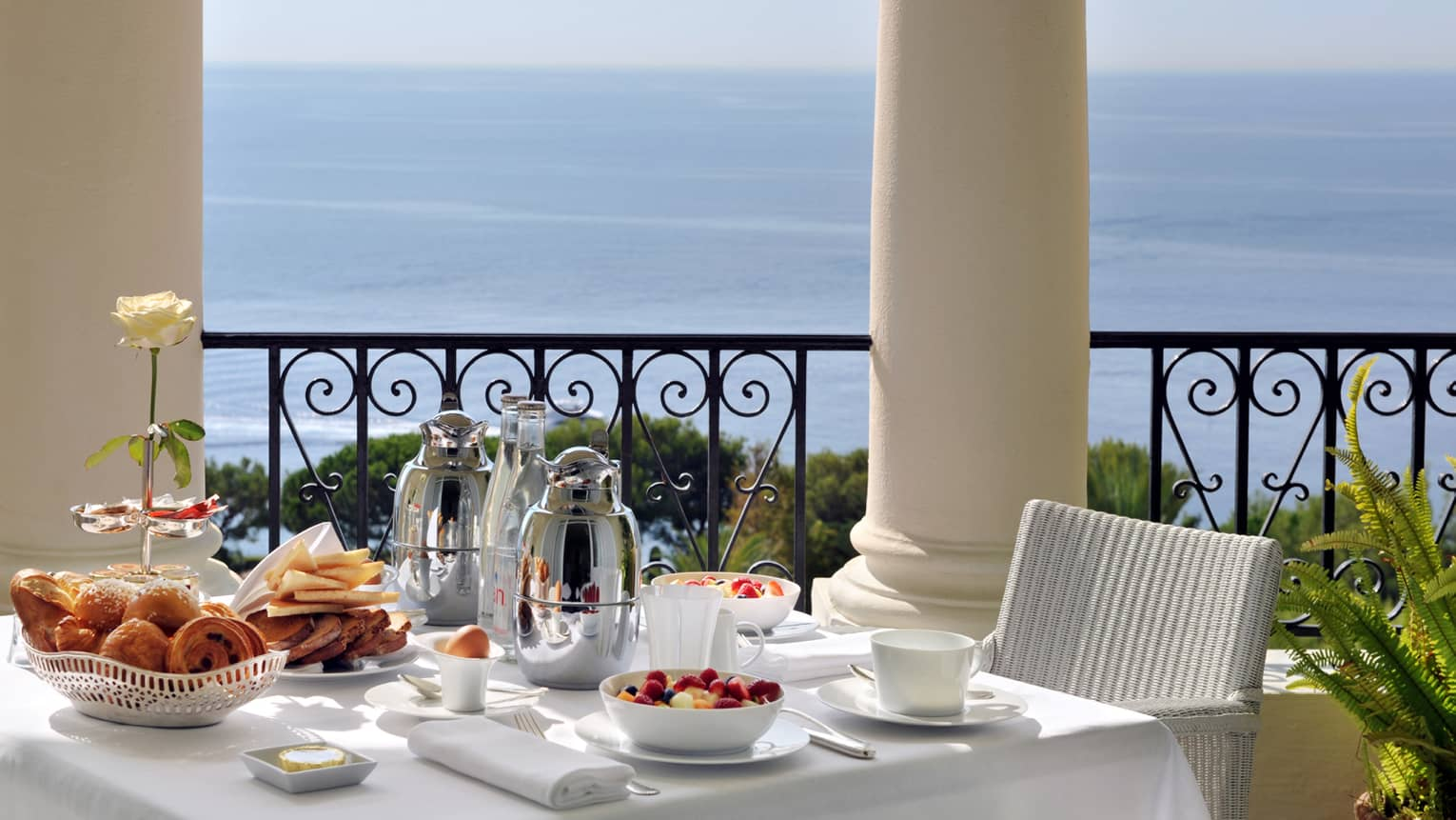 Brunch is arranged on a square table with white table cloth, white whicker chair on balcony overlooking the sea