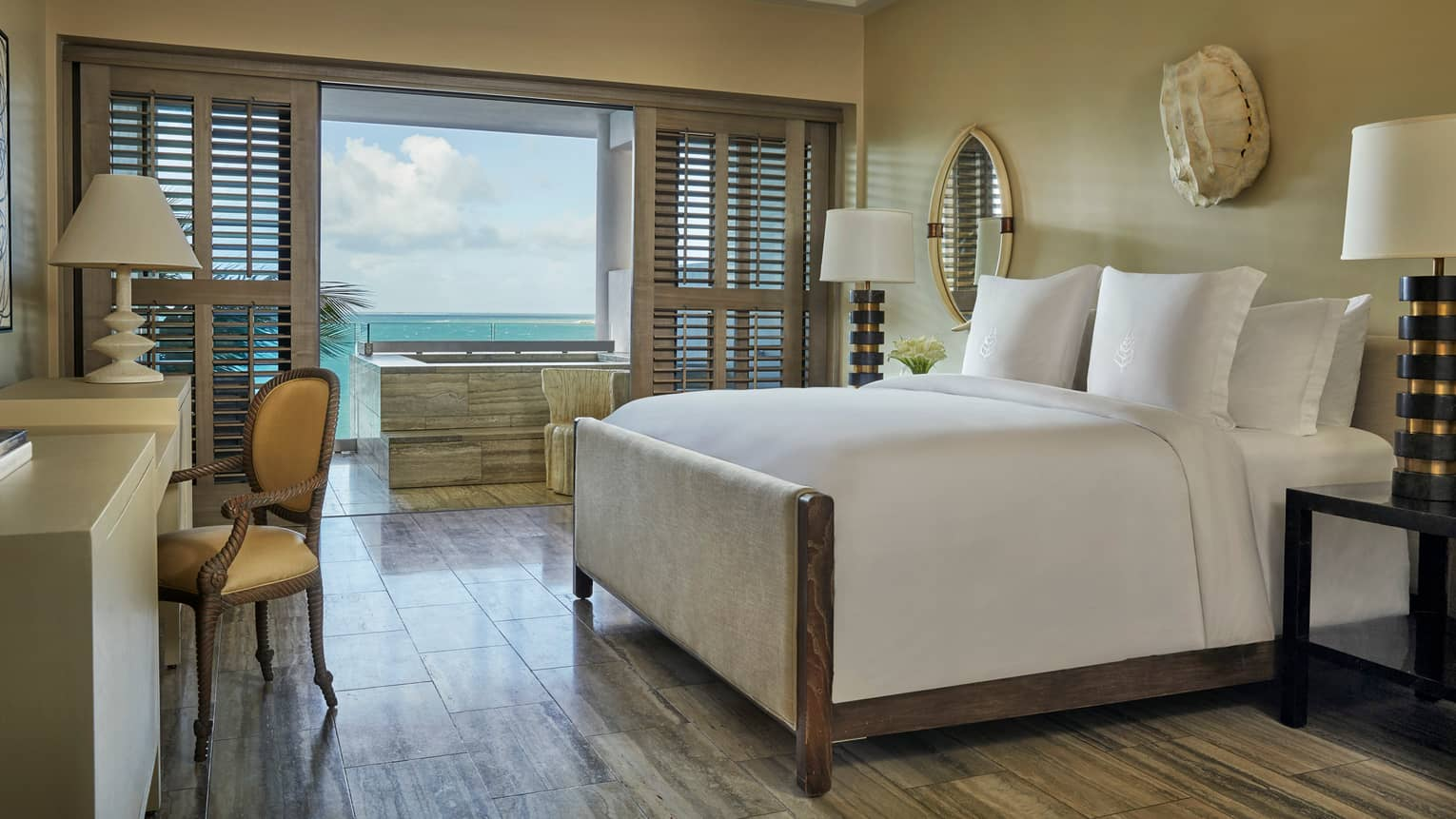 Ocean-View Studio Room bed, desk, bedside lamps, white wall sculpture, patio doors with wood shutters