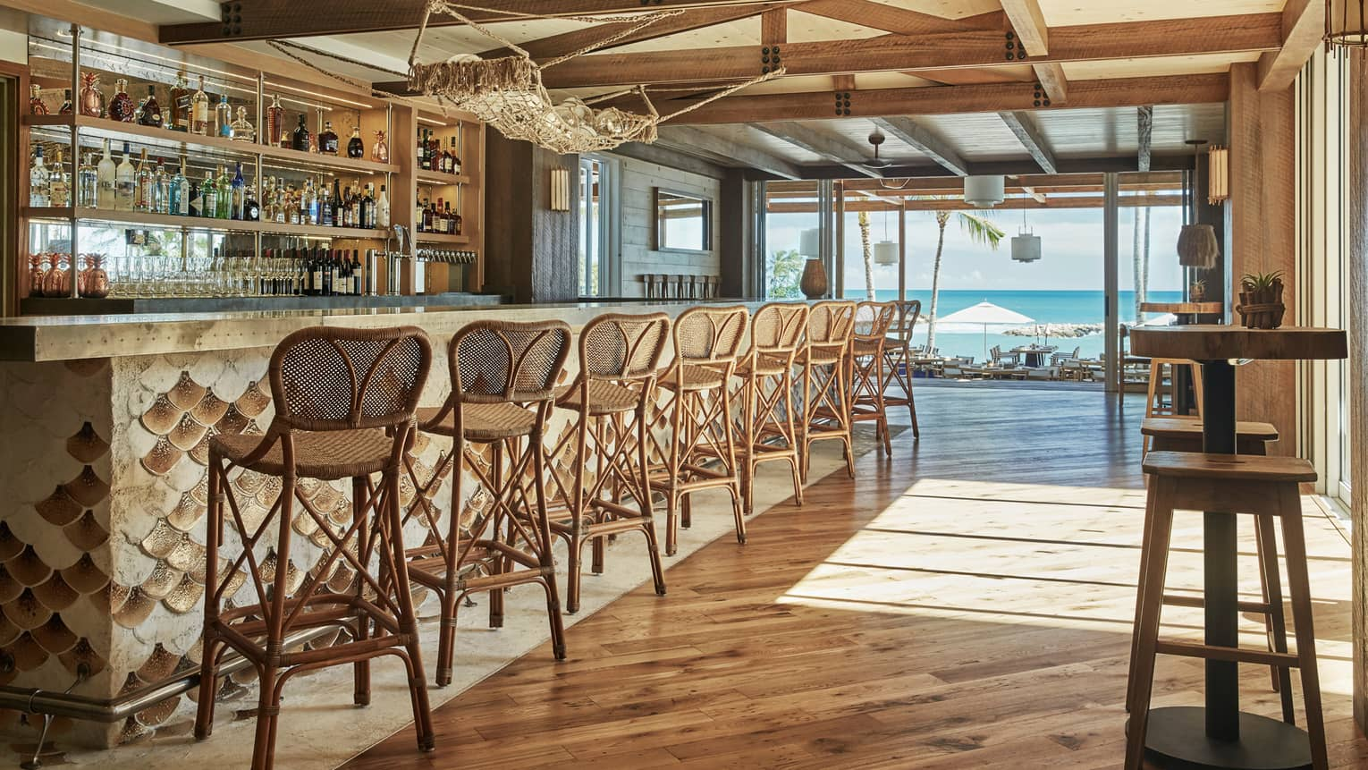 Wicker stools line Minas bar with wood fish-scale design, under fish net hammock with glass balls
