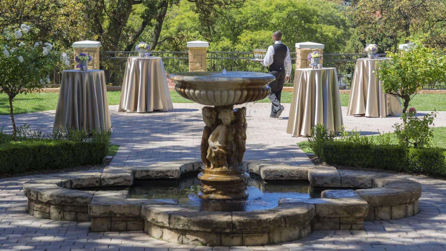 Fountain in garden event space dotted with small cocktail tables