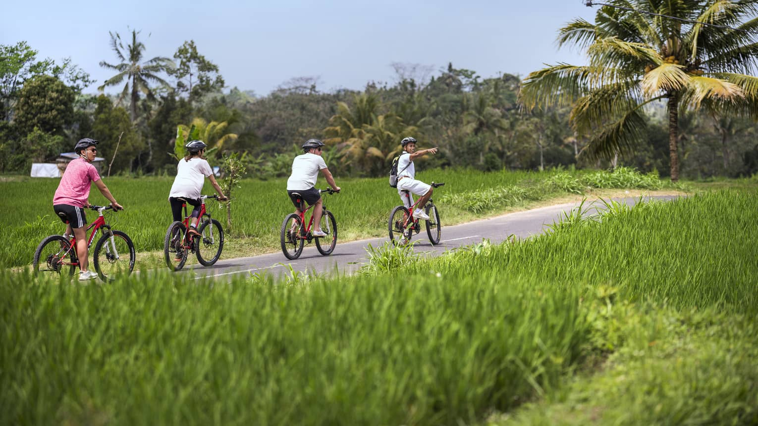 Four seasons guests bike along a paved path near four seasons hotel bali at sayan