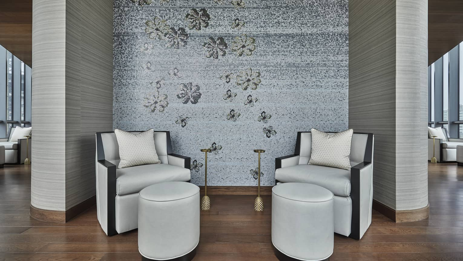 Two white leather chairs site in a corner of the Wellness Floor of Four Seasons Onedalton