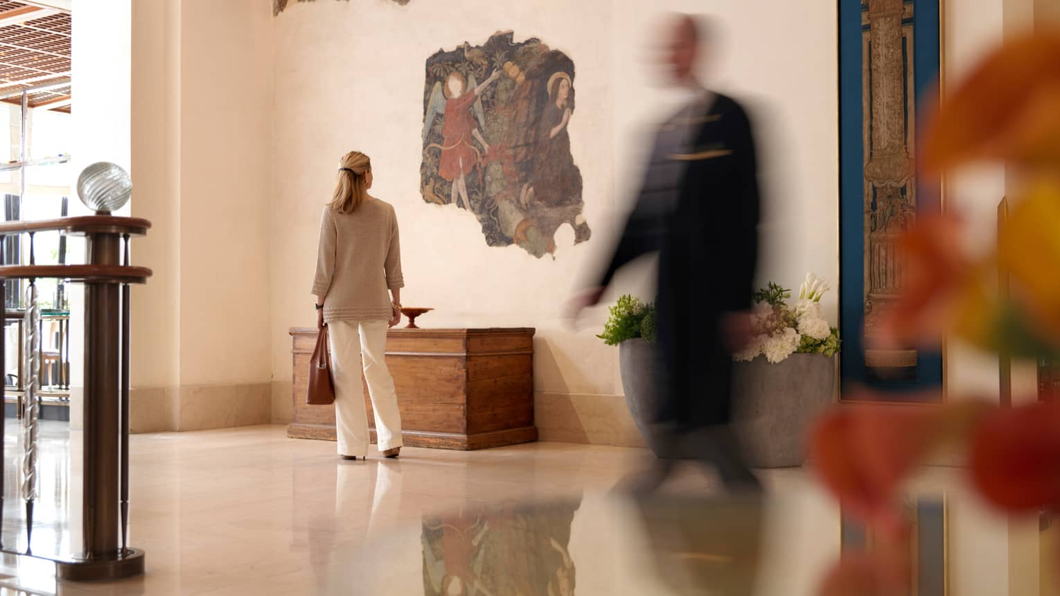 Woman holds purse, looks at angel mural in hotel lobby halls