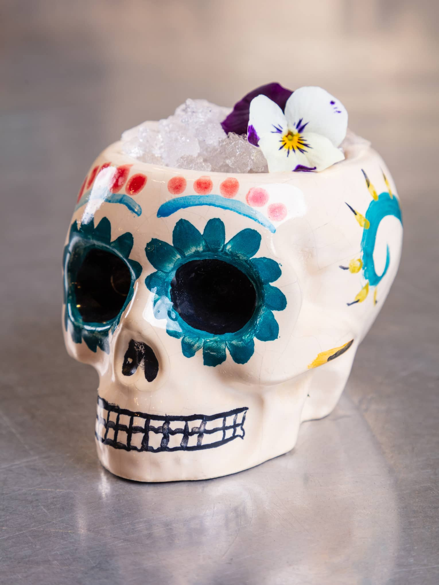A cocktail is served in a hand-painted ceramic skull glass