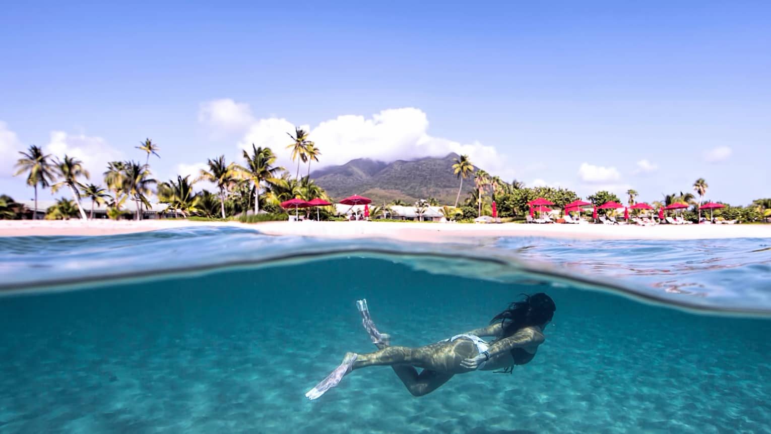Underwater view of woman swimming with flippers, beach and resort on shore above