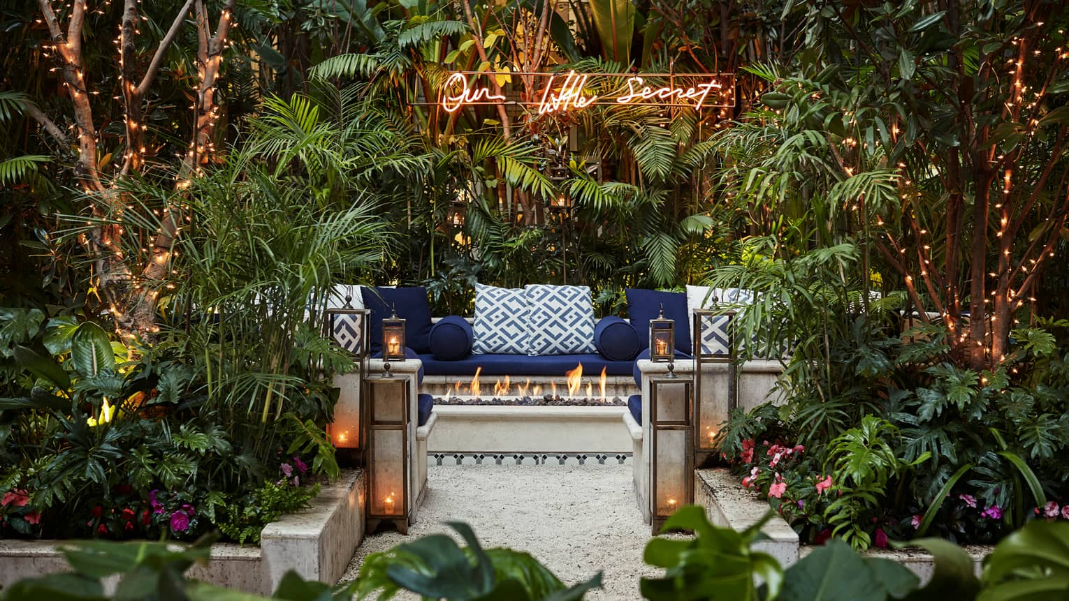Our Little Secret sign over cushioned bench behind outdoor fireplace, lanterns, tropical garden