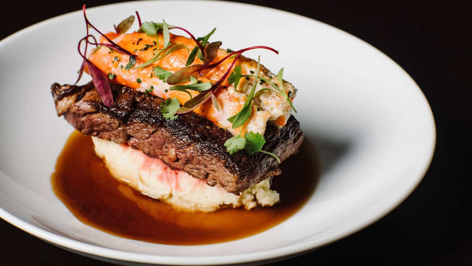 Close-up of grilled steak topped with lobster and fresh herbs, on bed of mashed potato with jus