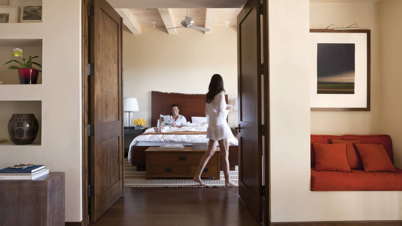 Hotel suite modern wood doors open to man reading in bed, woman walking with coffee cup