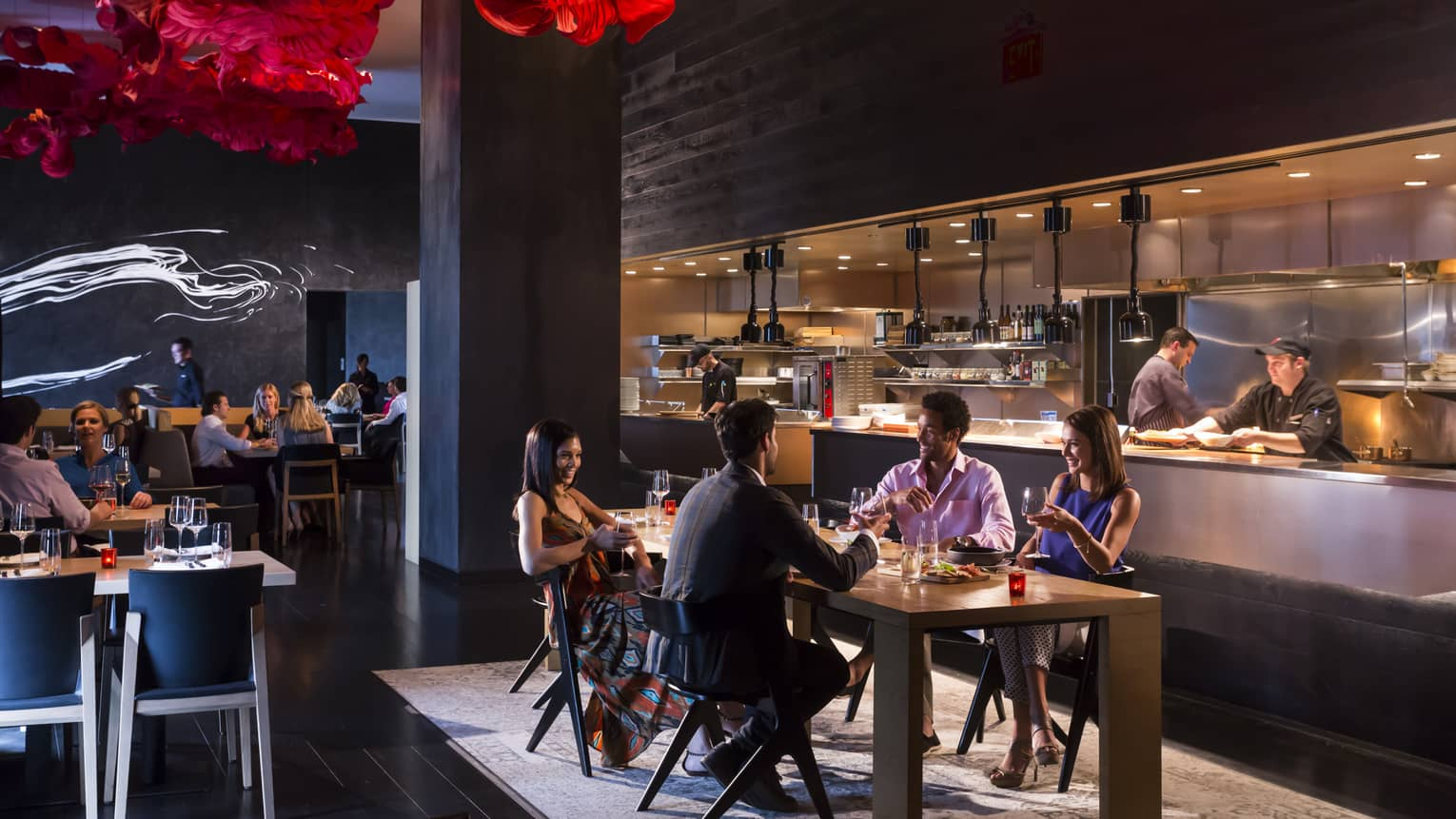 Guests dine in a dimly lit room, red sculptural accents hang on the ceiling, chefs prepare food in an open kitchen