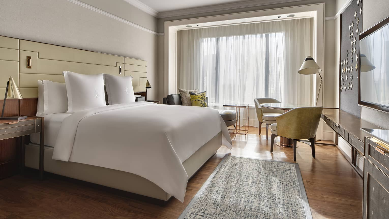 Light-filled hotel room with white king bed, wood floors and rug, two arm chairs, sheer curtains