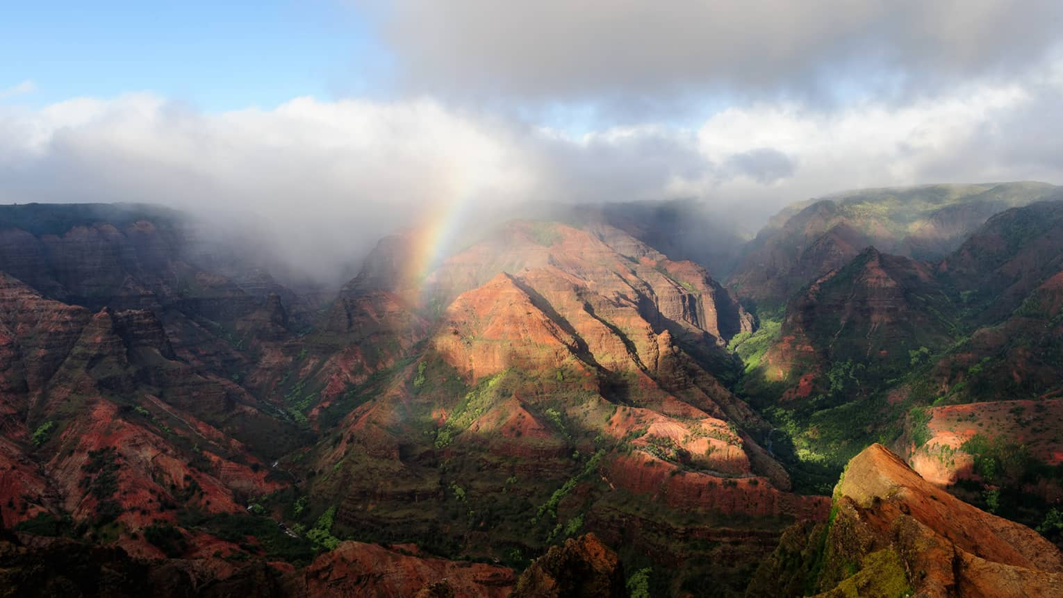 Sweeping views of The Waipi'o Valley Lookout mountains with clouds, rainbows