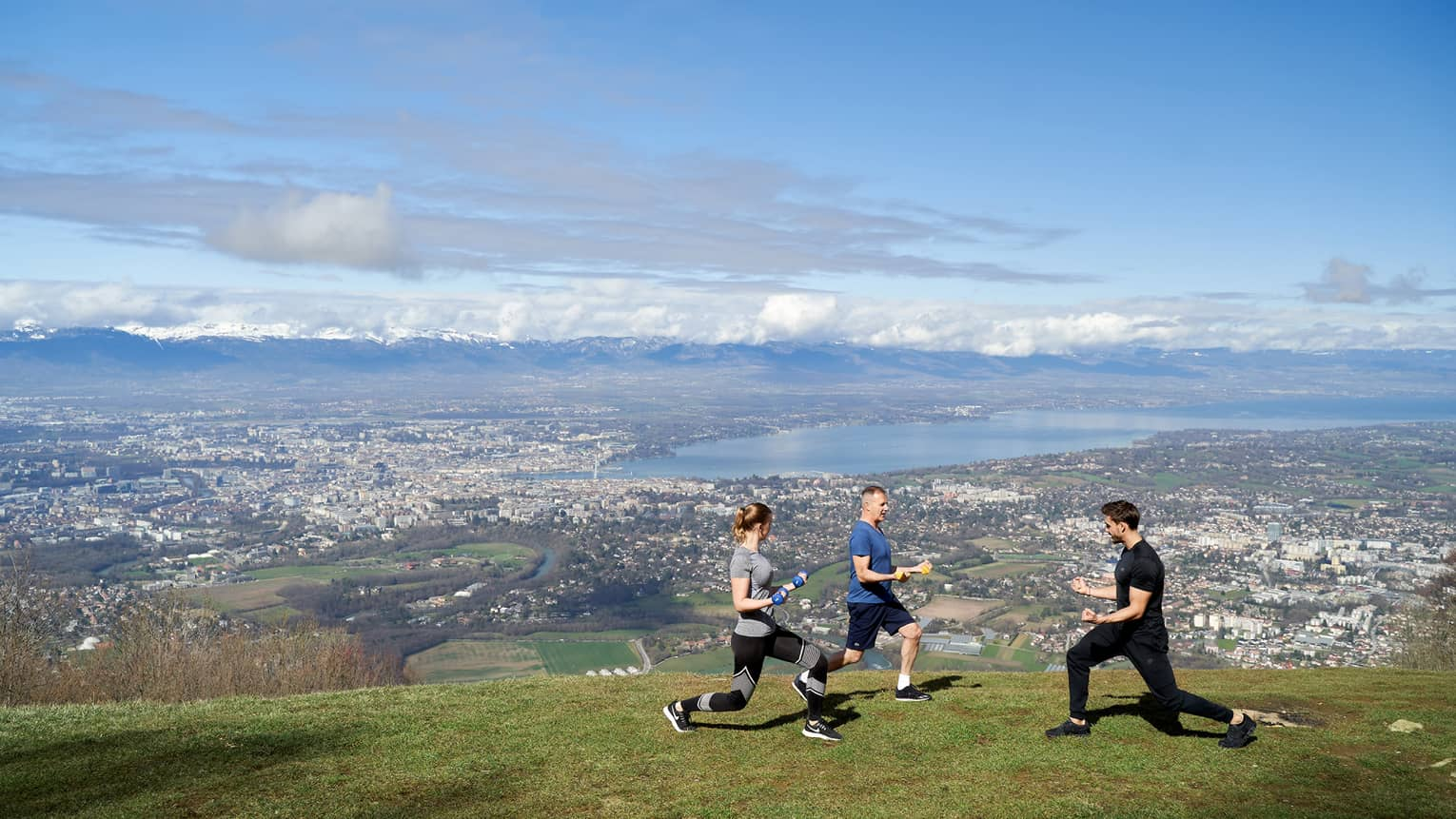 Two people on green mountainside doing knee bends with trainer and blue skies in background