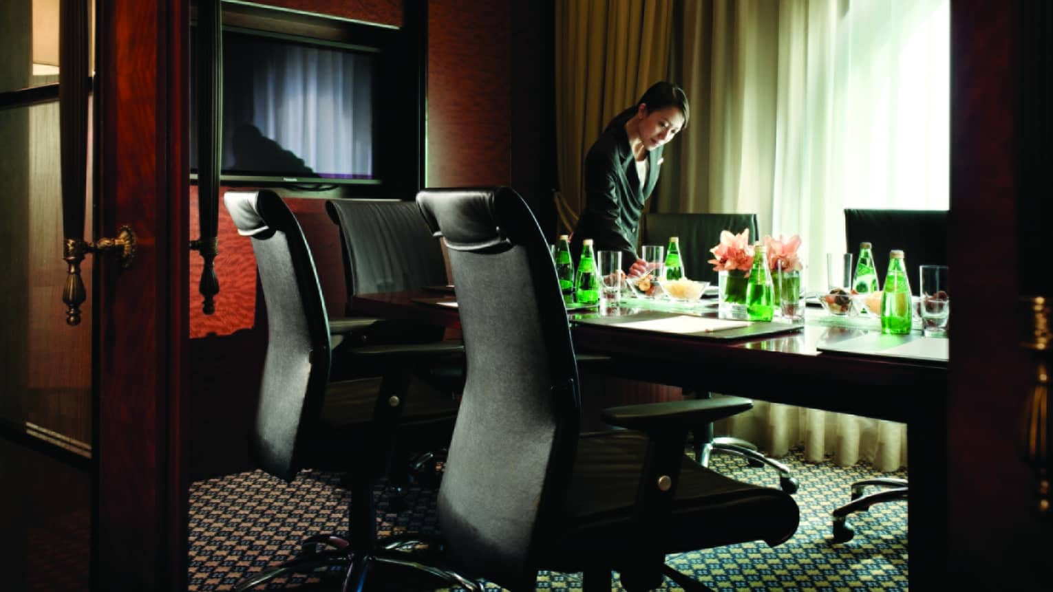 Woman sets water glass on Executive Lounge Meeting Room boardroom table
