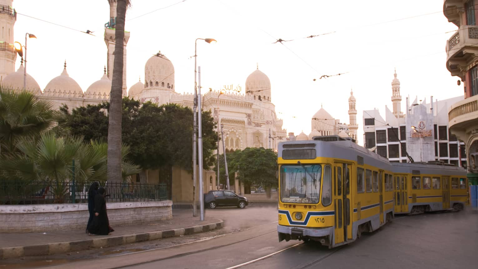 Yellow trolley car on track in front of El-Mursi Abul Abbas Mosque on sunny day