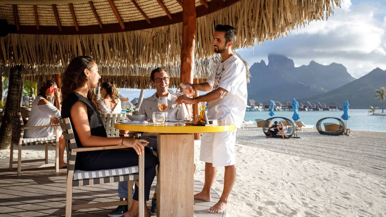 Staff refills wine for couple at patio table on white sand beach