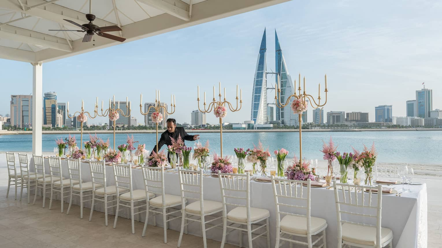 Hotel staff sets long wedding dining table by waterfront, city skyline in background