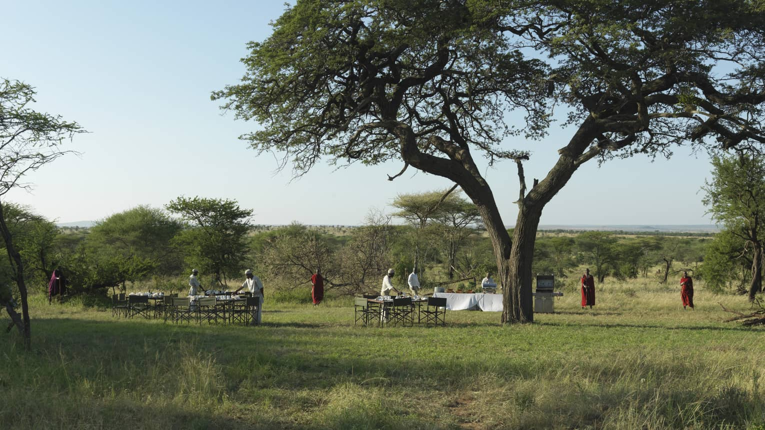 Staff set outdoor table and chairs as Maasai stand nearby at the outdoor meeting pit