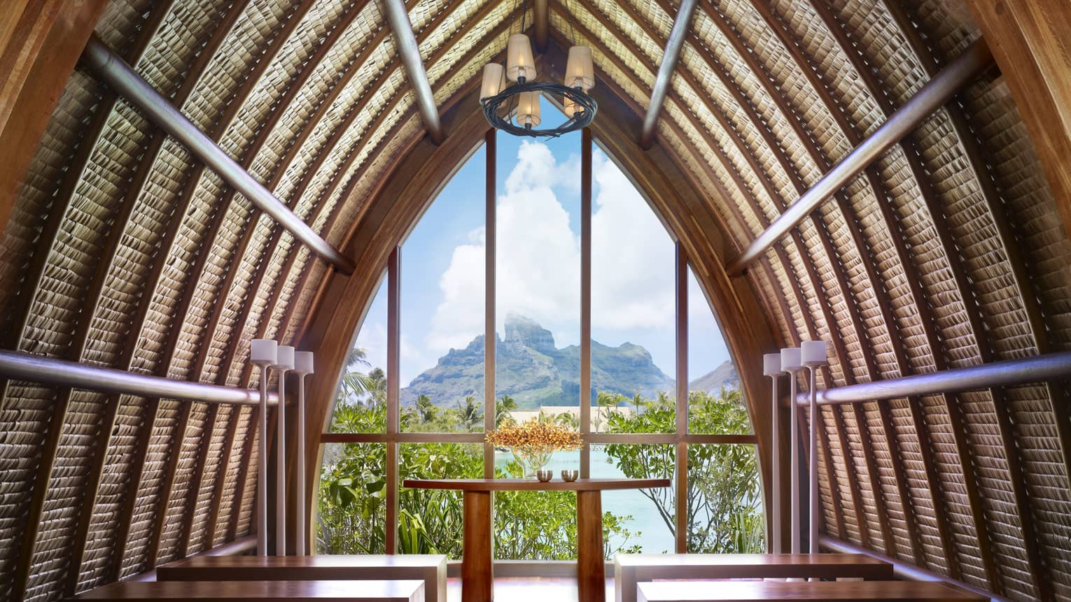 Arched roof of Aherenona chapel with end window looking over resort, lagoon and mountain