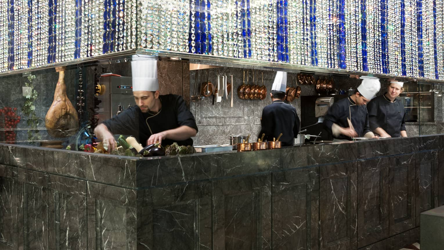Chefs in uniform work behind black marble open kitchen at Percorso restaurant