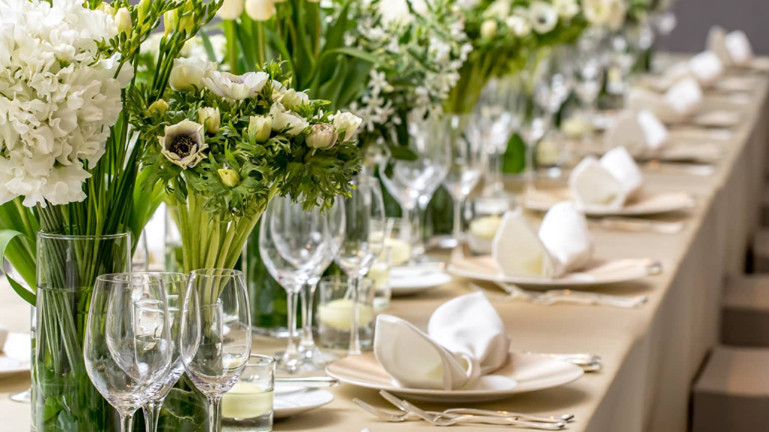 Close-up of long wedding dining table with wine glasses, white flowers in vases
