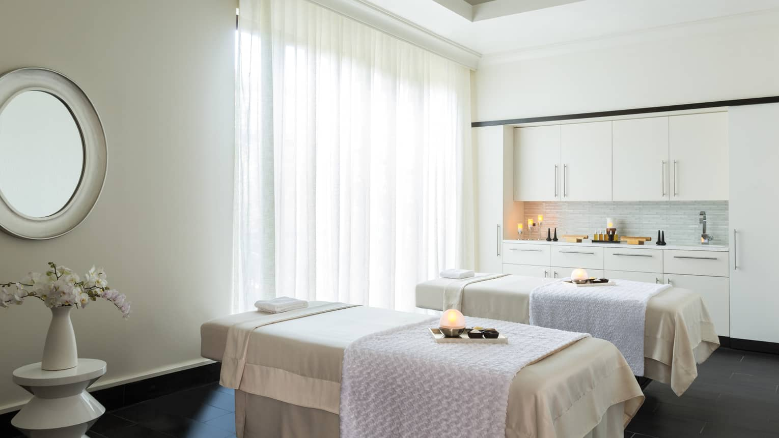 Couples Suite two massage tables with trays with glowing candles, salts in spa treatment room