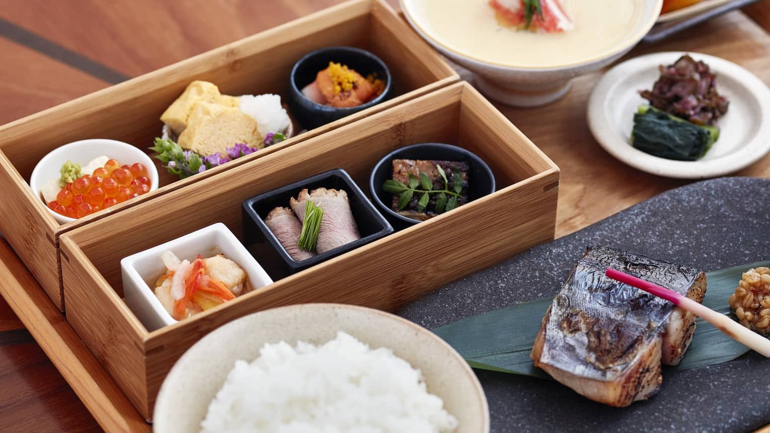 A close up of a Japanese Breakfast on a natural wooden tray – sushi, chopsticks, sashimi, caviar and peaches