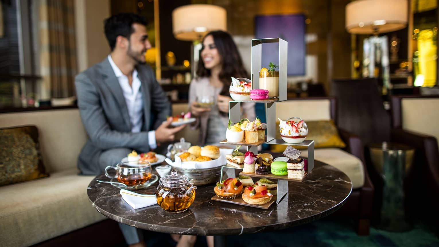Coffee table with afternoon tea service, three-tiered tray with fine desserts, couple on sofa in background