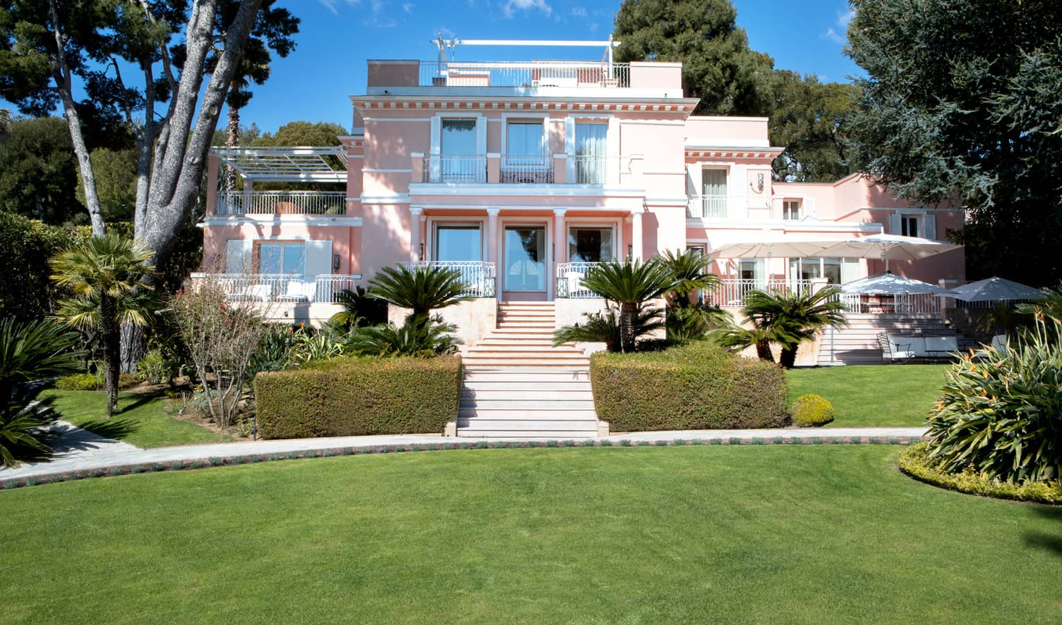 Manicured gardens, steps up to large three-storey pink villa